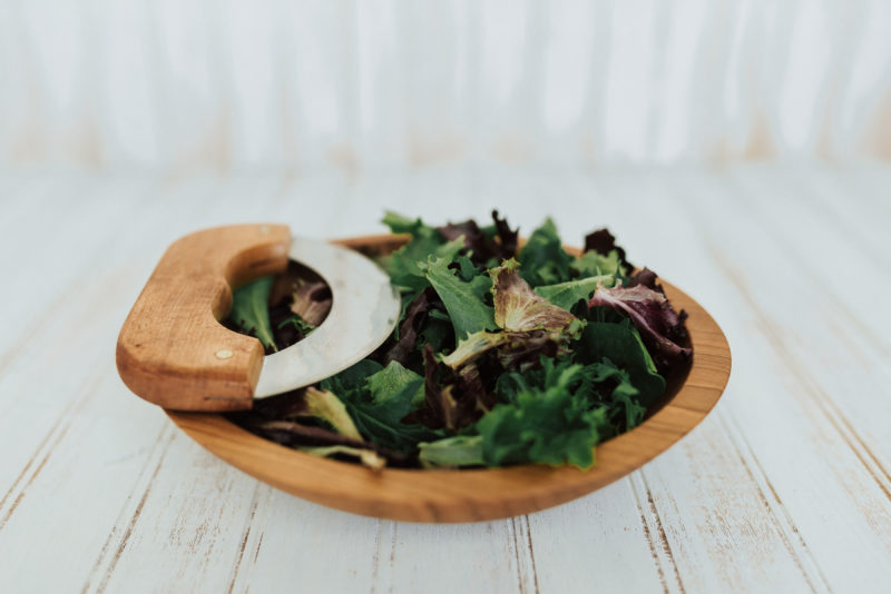 A 9-inch small chopping bowl set with Cherry bowl and mezzaluna knife. Shown with pre-chopped salad