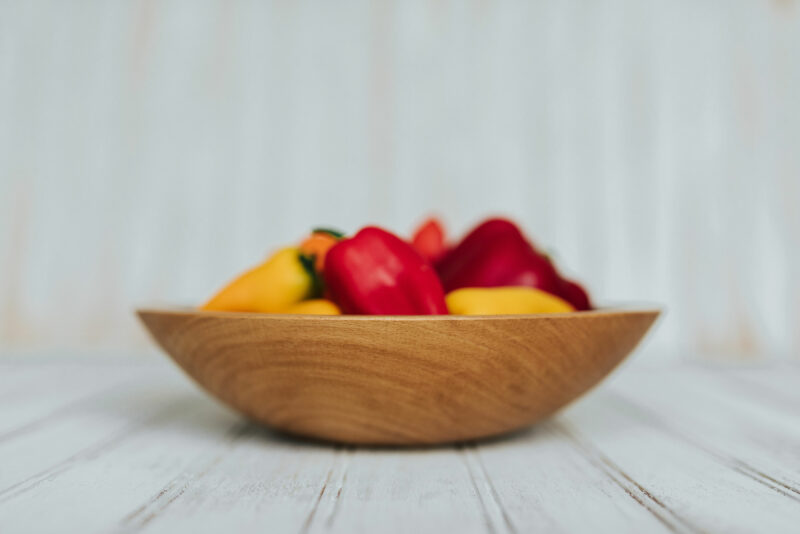 9-inch Beech large wooden snack bowl filled with tiny red and yellow peppers