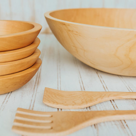 A Maple wood salad bowl set featuring four 7-inch bowls, one 17-inch bowl, and 14-inch utensils