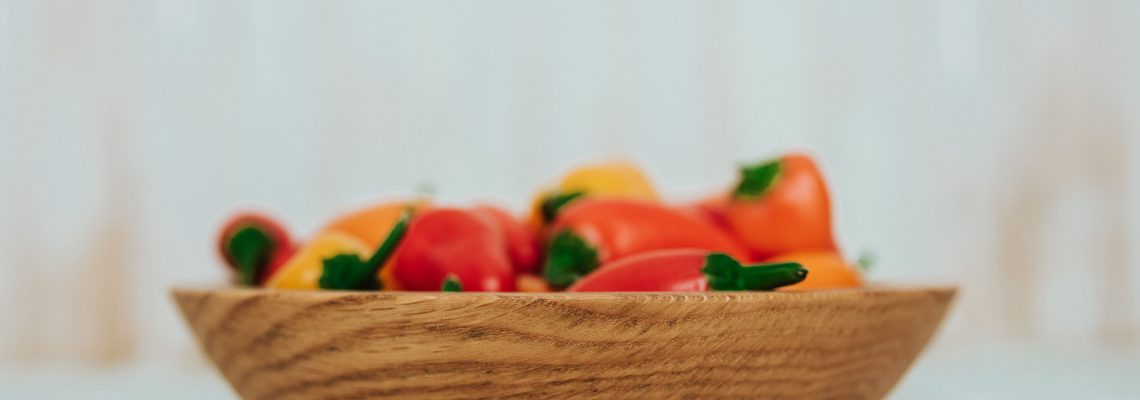 One of Holland Bowl Mill's durable wooden bowls holding some assorted peppers.