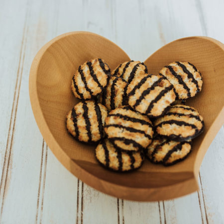 A tear drop bowl that is heart shaped, holding a macaroons.