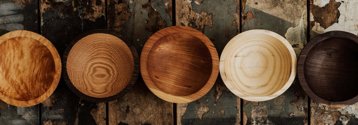 Five wood turning bowls lined up on a rustic table.