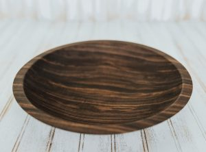 A shallow yet large wooden plate made from walnut.