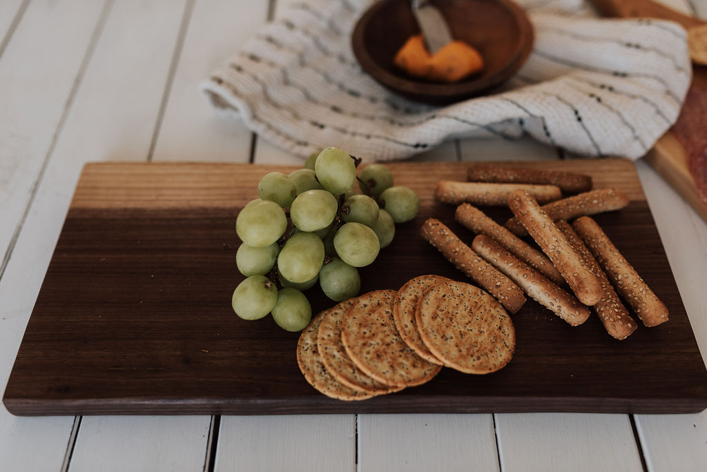 A wood cytting and serving board by the Holland Bowl Mill, with grapes, crackers, pretzels, and spreading cheese. Fixing a warped cutting board takes time, but with proper care, can be easily achieved.