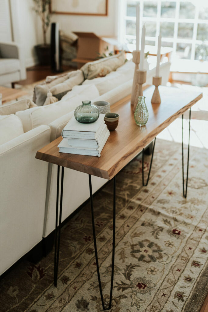 Natural wood furniture options from the Holland Bowl Mill include a console table that can sit inline with the backing a white sofa (as shown).