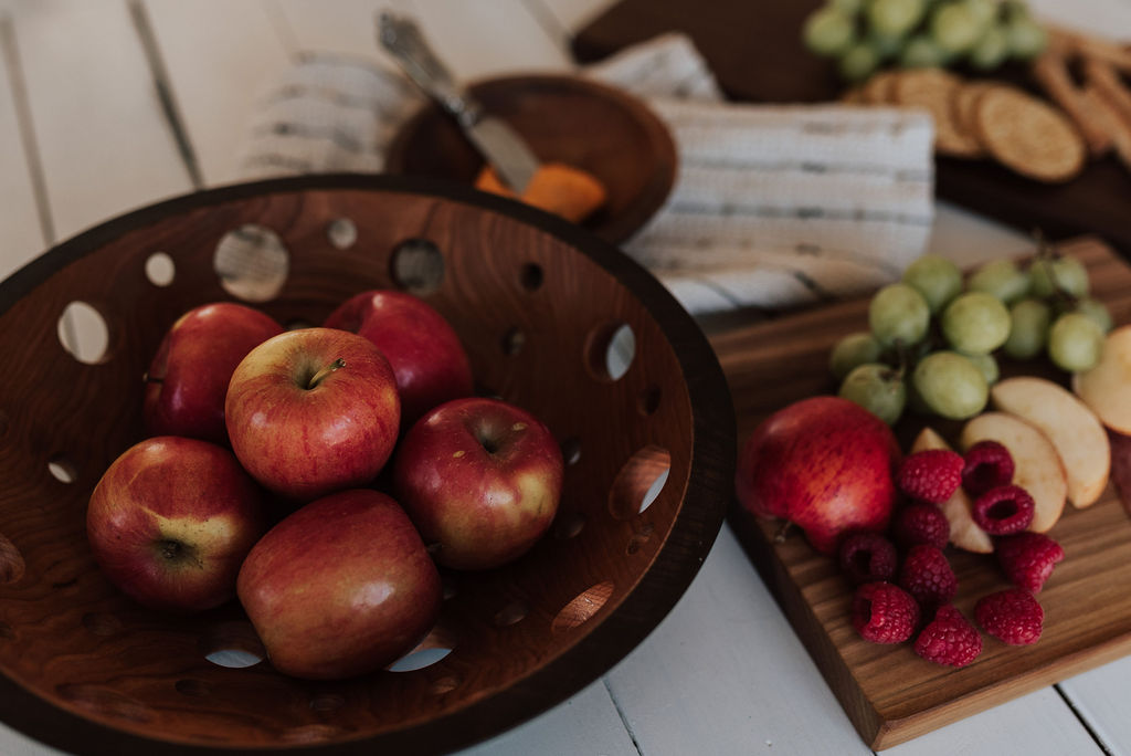 What is a fruit bowl? Fruit bowls have holes cut into them at strategic locations to ensure fruit lasts longer and doesn't droop or bruise. Six apples in a dark walnut fruit bowl.