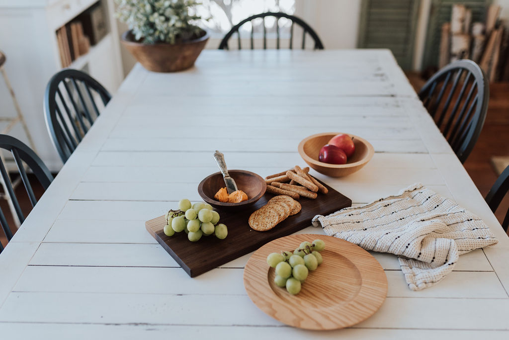 Wooden plates are just as durable as our bowls and boards. A wooden plate with grape son it next to a charcuterie board with cheese and crackers.