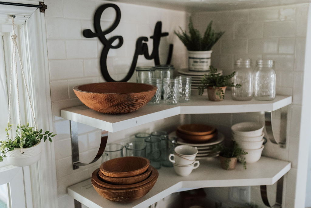 Wooden serving bowls stacked in a kitchen shelving unit.