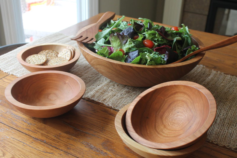 Wooden bowls on a dinner table with a full salad.